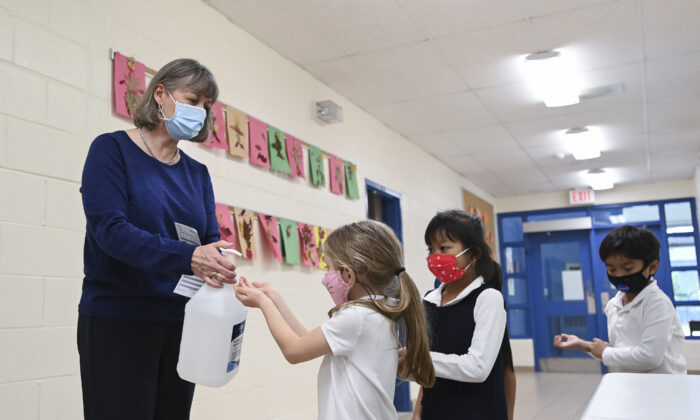 Children sanitize their hands while physical distancing after getting their pictures taken at picture day at St. Barnabas Catholic School during the COVID-19 pandemic in Scarborough, Ont., Canada, on Oct. 27, 2020. (Nathan Denette/The Canadian Press)