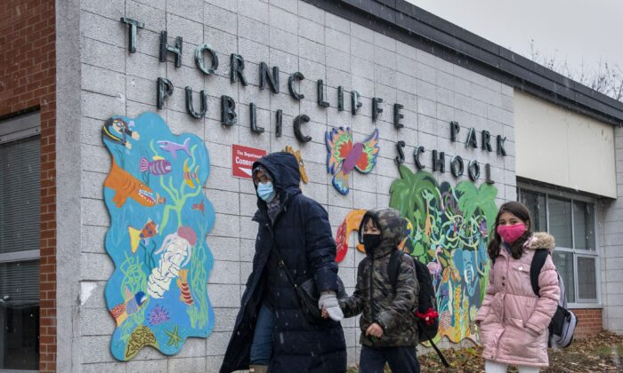 A family walk past the sign at Thorncliffe Park Public School in Toronto, Canada, on Dec. 4, 2020. (Frank Gunn/The Canadian Press)