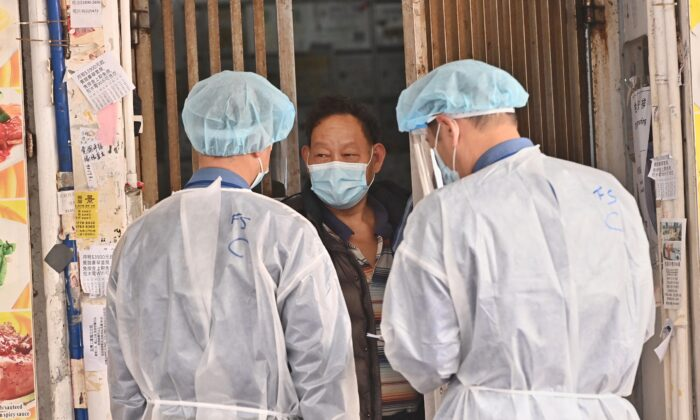 A resident in Hong Kong's Jordan restricted area asks medical workers about food supplies on Jan. 24, 2021. (Adrian Yu/Epoch Times)