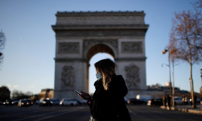 A woman, walks past Champs Elysees avenue near the Arc de Triomphe in Paris, in France, on Jan. 25, 2021. (Gonzalo Fuentes/Reuters)