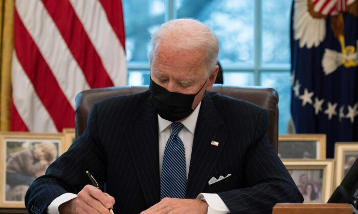 President Joe Biden signs an executive order in the Oval Office of the White House on Jan. 25, 2021. (Jim Watson/AFP via Getty Images)