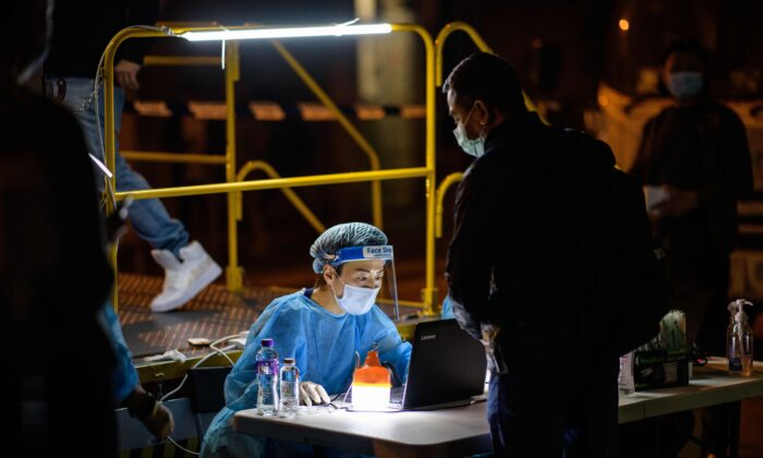 A resident registers for a mandatory COVID-19 test with a health worker wearing protective gear at a testing site in the Jordan area of the Yau Tsim Mong district of Kowloon in Hong Kong on Jan. 22, 2021. (ANTHONY WALLACE/AFP via Getty Images)