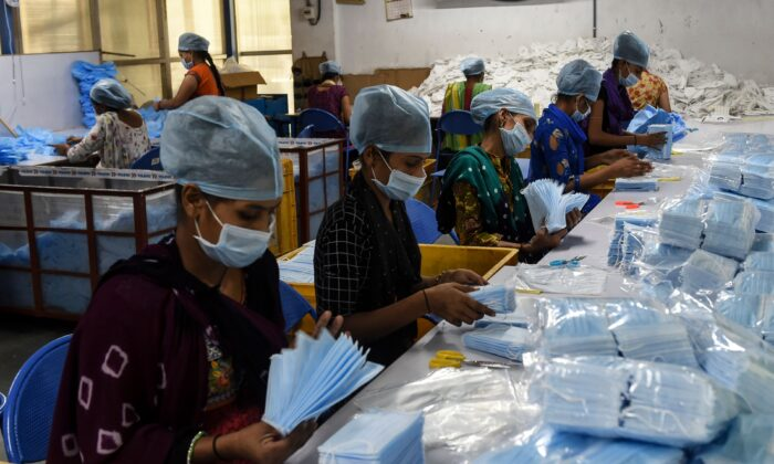 Employees pack surgical facemasks at a factory near Changodar, some 20 kms from Ahmedabad, India, on Nov. 8, 2020. (SAM PANTHAKY/AFP via Getty Images)