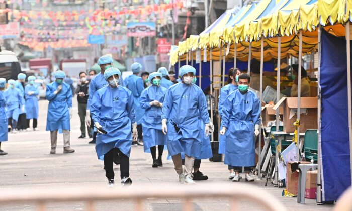 Medical workers walk on Temple Street in the lockdown area of Jordan in Hong Kong, on Jan. 24, 2021. The Hong Kong government recently enacted mainland-style lockdowns in its efforts to curb the spread of COVID-19. (Adrian Yu/Epoch Times)