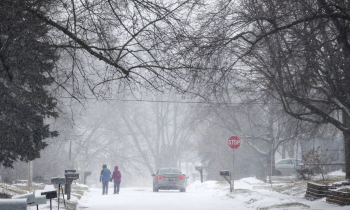 Two people hold hands while walking south on Madison Street toward 27th Avenue in Bellevue, during a winter storm warning, Neb., on Jan. 25, 2021. (Chris Machian/Omaha World-Herald via AP)