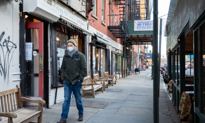 "A man wearing a protective face mask walks past stores showing ""No mask, no entry"" signs, in New York on Jan. 20, 2021. (Chung I Ho/The Epoch Times)"