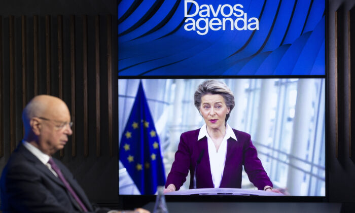 German Klaus Schwab, left, Founder and Executive Chairman of the World Economic Forum, WEF, listens to European Commission President Ursula von der Leyen, displayed on a video screen, during a conference at the Davos Agenda in Cologny near Geneva, Switzerland, on Jan. 26, 2021. (Salvatore Di Nolfi/Keystone via AP)