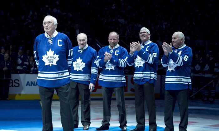 Toronto Maple Leafs alumni applaud fellow alumni George Armstrong (L) during a ceremony before the Toronto Maple Leafs and Winnipeg Jets NHL game in Toronto on Feb. 21, 2015. Armstrong died on Jan. 24, 2020. (The Canadian Press/Darren Calabrese)