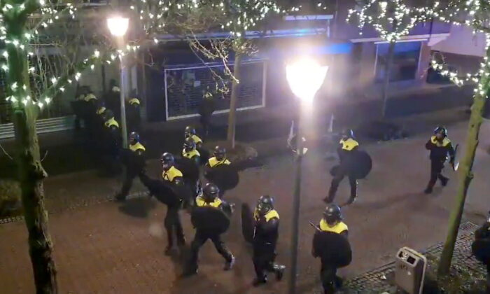 Police officers and vehicles arrive to disperse people from the site of one of the COVID-19 curfew protests in Geleen, Netherlands, on Jan. 25, 2021, in this still image from video obtained from social media. (Evert Bopp via Reuters)