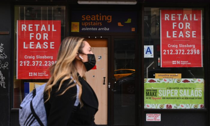 A woman walks past a closed retail store for lease in midtown Manhattan in New York City on Jan. 25, 2021. (Angela Weiss/AFP via Getty Images)