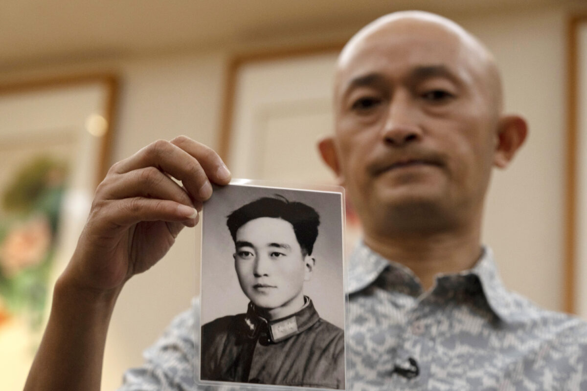 Zhang Hai holds up a photo of his father