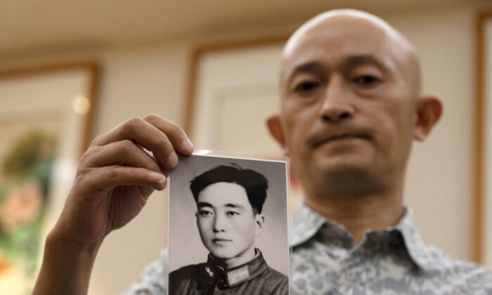 Zhang Hai holds up a photo of his father taken in his youth during an interview in Shenzhen in southern China's Guangdong province on Oct. 16, 2020. (Ng Han Guan/AP Photo)