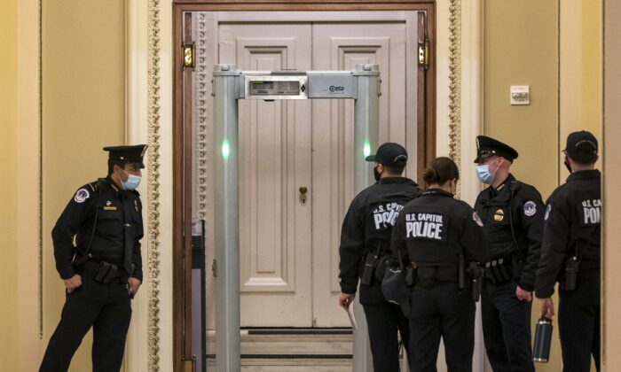 U.S. Capitol Police survey the corridor around the House of Representatives chamber after enhanced security protocols were enacted, including metal detectors for lawmakers, after protesters stormed the Capitol, in Washington on Jan. 12, 2021. (J. Scott Applewhite/AP Photo)