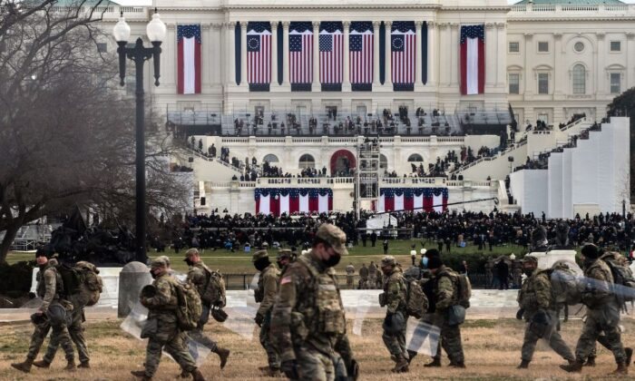 National Guard troops carry riot shields as they assume positions in the vicinity of the US Capitol as the Inauguration of Joe Biden in Washington, on Jan. 20, 2021. (Roberto Schmidt/AFP via Getty Images)