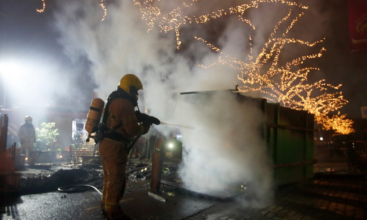 A firefighter extinguishes a container