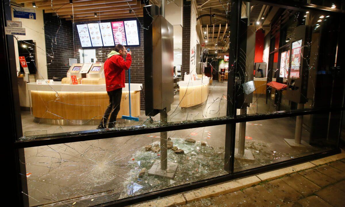 A man cleans up broken glass