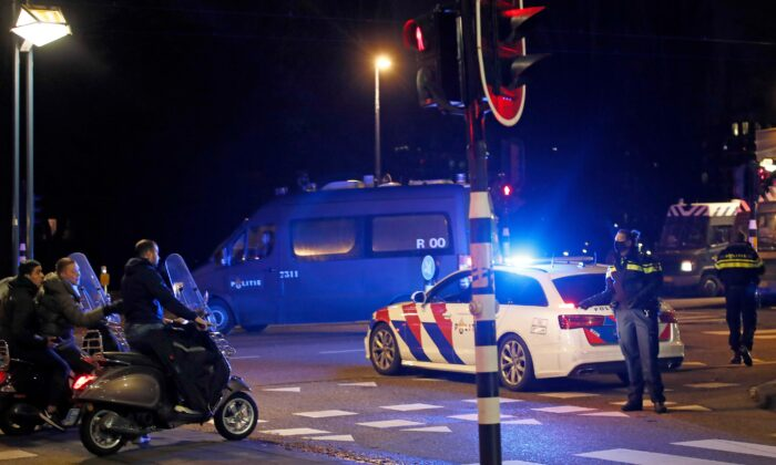 A police officer speaks to youths on scooters at a road block during a nation-wide curfew in Amsterdam, Netherlands, on Jan. 26, 2021. (Peter Dejong/AP Photo)