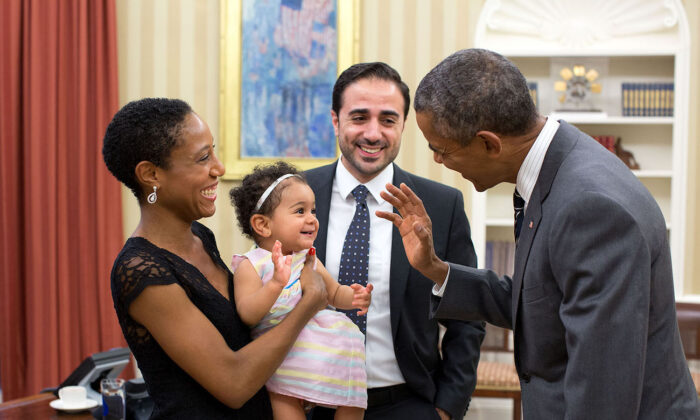 President Barack Obama greets Alya Dorelien Bitar, the 1-year-old daughter of Maher Bitar, the outgoing National Security Council Director for Israeli and Palestinian Affairs, and his wife, Astrid Dorelien, during a family photo in the Oval Office, on Sept. 21, 2015. (White House/Pete Souza)