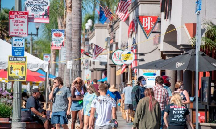 A sign advises people to maintain social distancing, July 16, 2020, in Huntington Beach, Calif., amid the coronavirus pandemic. (Photo by Robyn Beck/AFP via Getty Images)
