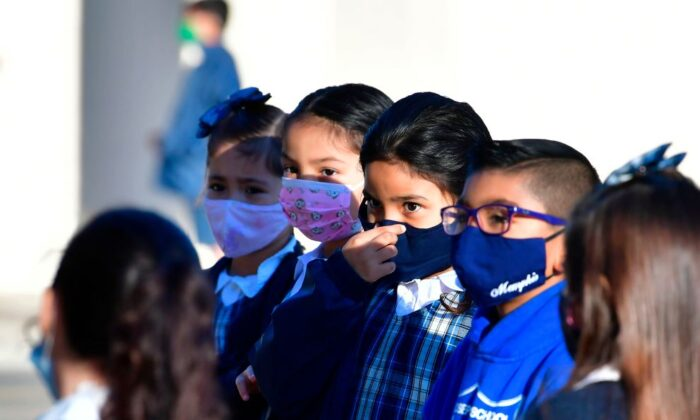 A student adjusts her face mask at St. Joseph Catholic School in La Puente, Calif., on Nov. 16, 2020. (Frederic J. Brown/AFP via Getty Images)