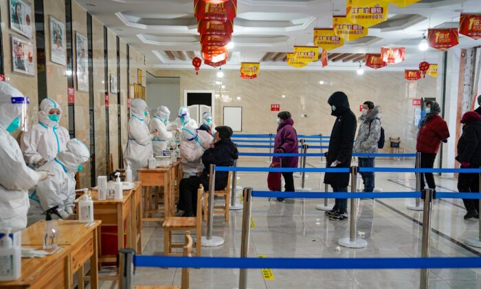 """A medical worker takes a swab sample from a man as people queue to get tests for Covid-19 coronavirus at an office building in Harbin, in northeastern China's Heilongjiang province on Jan. 14, 2021, after the province declared an """"emergency state"""" as daily Covid-19 numbers climb. (STR/AFP via Getty Images)"""