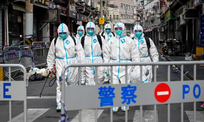 Health workers walk out from a blocked off area after spraying disinfectant in Huangpu district, Shanghai, China, on Jan. 27, 2021. (STR/AFP via Getty Images)