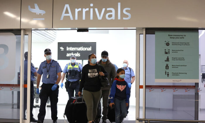 PERTH, AUSTRALIA - OCTOBER 19: Passengers from Qantas flight QF583 are escorted to waiting Transperth buses by Police Officers after being processed following their arrival at Perth Airport from Sydney, before being driven to a CBD hotel for quarantining on October 19, 2020 in Perth, Australia. Paul Kane/Getty Images)