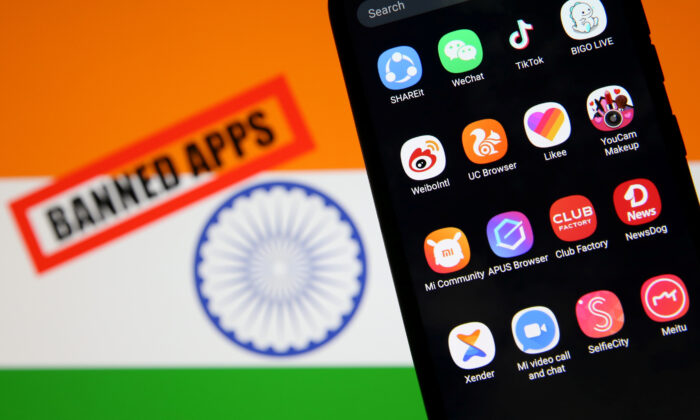 """Smartphone with Chinese applications is seen in front of a displayed Indian flag and a """"Banned app"""" sign in this illustration picture taken on July 2, 2020. (Dado Ruvic/Illustration/Reuters)"""