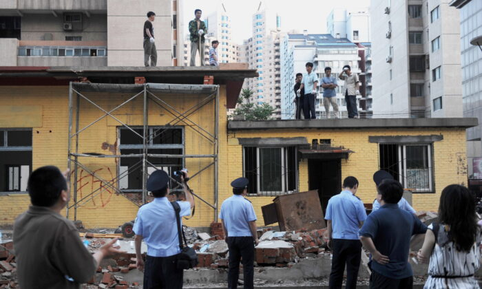 Chinese police film workers demolishing a group of buildings. Local residents claim the land belonged to their community and was were illegally built upon by a property company, in Beijing on May 31, 2010. (STR/AFP via Getty Images)