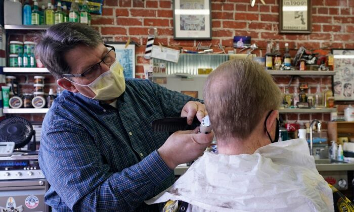 Mike Douglass (L) gives Kent Kjestrom a haircut at East J Barbers in Sacramento, Calif., on Jan. 21, 2021. (Rich Pedroncelli/AP Photo)