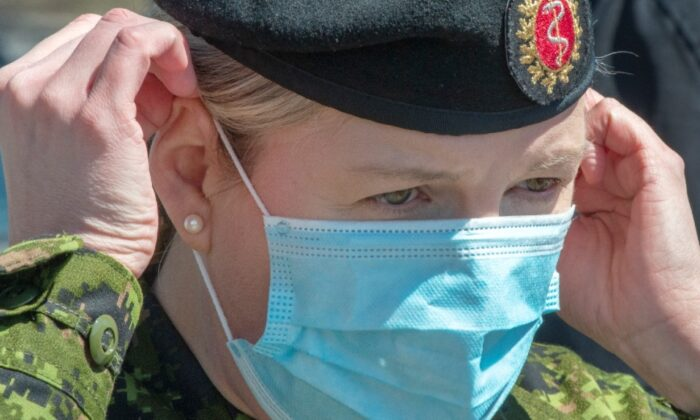 Canadian Armed Forces Lt. Cmdr. Heather Galbraith puts on a mask as she arrives at the Villa Val des Arbes seniors residence in Laval, Que., on April 20, 2020. (Ryan Remiorz/The Canadian Press)