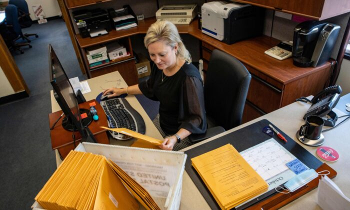 Barbara Johnston in the Wood County Clerk's office sorts through mail-in ballots in Parkersburg, West Virginia, Va., on Oct. 21, 2020. (Stephen Zenner/AFP via Getty Images)