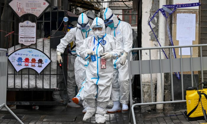 Health workers in protective gear walk out from a blocked off area after spraying disinfectant in Shanghai's Huangpu district on Jan. 27, 2021, after residents were evacuated following the detection of a few cases of COVID-19 coronavirus in the neighborhood. (STR/AFP via Getty Images)