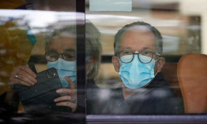 Peter Ben Embarek and Marion Koopmans, members of the World Health Organization (WHO) team tasked with investigating the origins of the coronavirus disease (COVID-19) pandemic, sit on a bus as they leave their quarantine hotel in Wuhan, Hubei province, China, on Jan. 28, 2021. (Reuters/Thomas Peter)