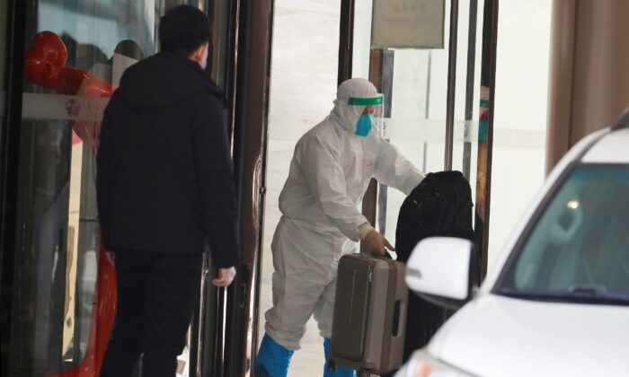 A staff member in protective gear moves luggage before members of the World Health Organization team tasked with investigating the origins of COVID-19 pandemic leave their quarantine hotel in Wuhan, Hubei Province, China, Jan. 28, 2021. (Thomas Peter/Reuters)