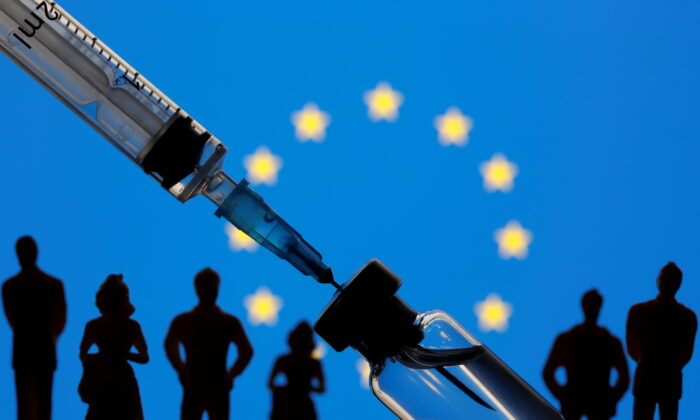 A vial, syringe, and small toy figures are seen in front of a displayed EU flag in this illustration taken Jan. 11, 2021. (Dado Ruvic/Illustration/Reuters)