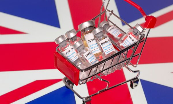 "A small shopping basket filled with vials labeled ""COVID-19 - Coronavirus Vaccine"" is placed on a UK flag"
