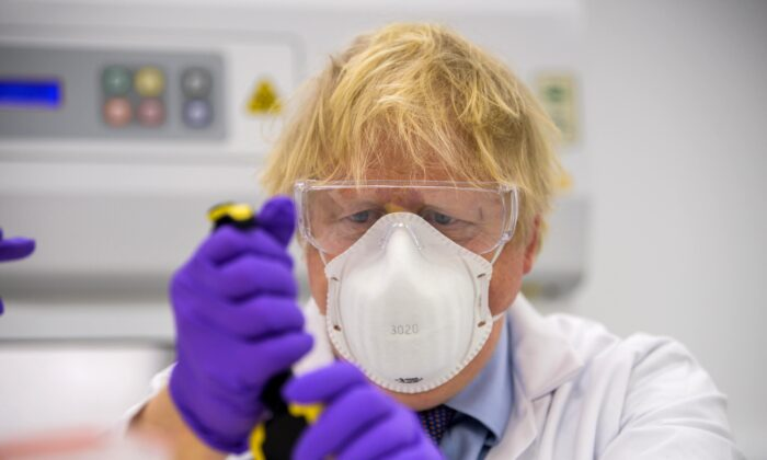 Boris Johnson tries his hand at one of the tests as he visits the French biotechnology laboratory Valneva in Livingston, Scotland, on Jan. 28, 2021. (Wattie Cheung-WPA Pool/Getty Images)