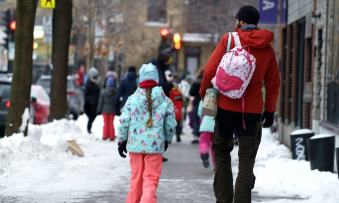 Parents walk their children to school as primary schools reopen following the Christmas break in Montreal on Jan. 11, 2021. (The Canadian Press/Paul Chiasson)