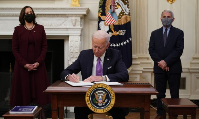 President Joe Biden signs executive orders as part of the Covid-19 response as Vice President Kamala Harris (L) and Director of NIAID Anthony Fauci look on in the State Dining Room of the White House in Washington on Jan. 21, 2021. (Mandel Ngan/AFP via Getty Images)