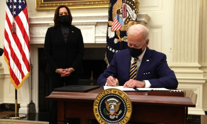 President Joe Biden signs an executive order as Vice President Kamala Harris looks on during an event on economic crisis in the State Dining Room of the White House in Washington Jan. 22, 2021. (Alex Wong/Getty Images)