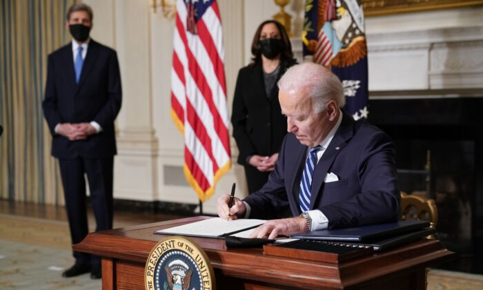 US Vice President Kamala Harris (2-L) and Special Presidential Envoy for Climate John Kerry (L) watch as US President Joe Biden signs executive orders after speaking on tackling climate change, creating jobs, and restoring scientific integrity in the State Dining Room of the White House on Jan. 27, 2021. (Mandel Ngan/AFP via Getty Images)