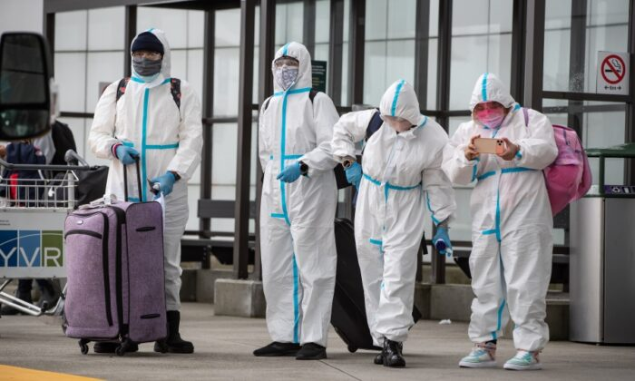 People wearing protective face masks, goggles and Tyvek suits who said they traveled from Colombia wait for a car rental company shuttle, after arriving at Vancouver International Airport in Richmond, B.C., on Dec. 31, 2020. (The Canadian Press/Darryl Dyck)