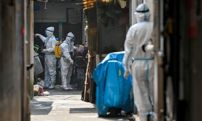 Health workers in protective gear spray disinfectant in a blocked off area in Shanghai's Huangpu district on Jan. 27, 2021, after residents were evacuated following the detection of a few cases of COVID-19 coronavirus in the neighbourhood. (STR/AFP via Getty Images)