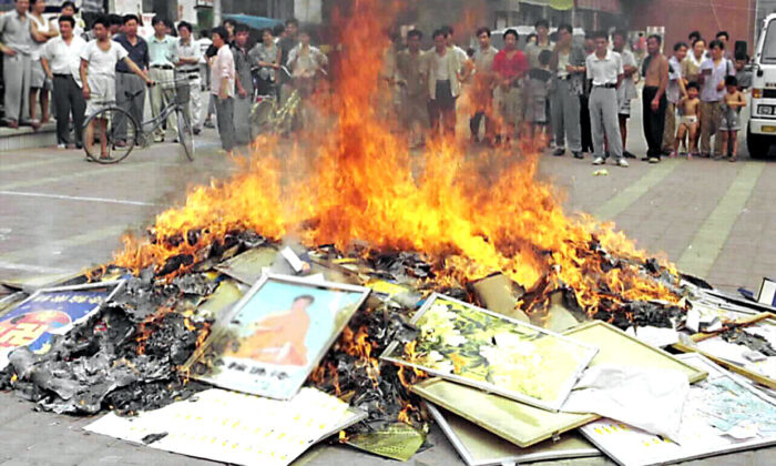 Falun Gong books and pictures are set on fire in Shouguang City, in China's Shandong Province, on Aug. 4, 1999. Chinese authorities in cities across China burned millions of Falun Gong books and materials after the communist regime launched a campaign to persecute the spiritual practice in July 1999. (STR/XINHUA/AFP via Getty Images)