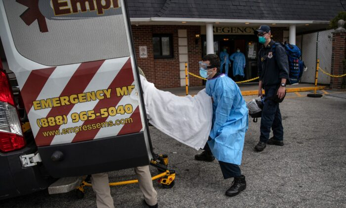 A medic from Empress EMS loads a suspected COVID-19 patient from the Regency Extended Care Center into an ambulance in Yonkers, N.Y., on April 7, 2020. (John Moore/Getty Images)