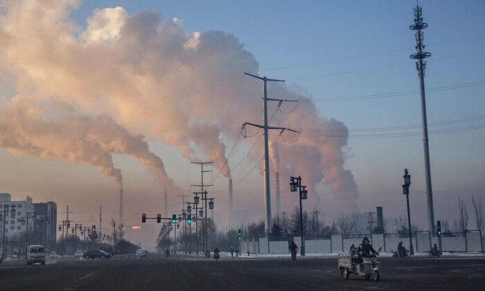 Chinese workers commute as smoke billows from a coal fired power plant in Shanxi, China, on Nov. 25, 2015. (Kevin Frayer/Getty Images)
