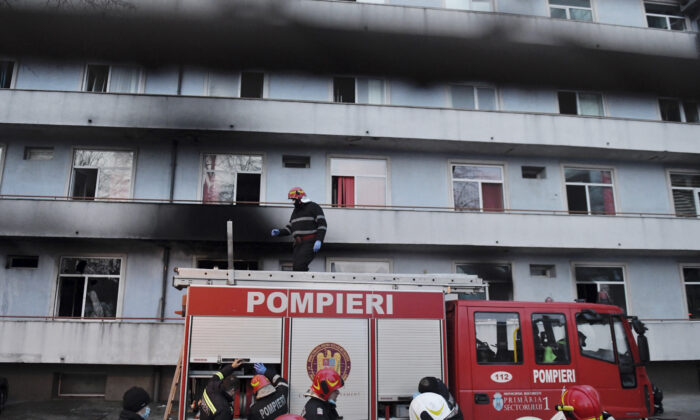 A firefighter stands on top of a fire engine outside a hospital after a fire broke out on the ground floor, Romania, on Jan. 29, 2021. (Andreea Alexandru/AP Photo)