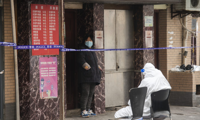 A health worker in a protective suit sits infront of a security line in the Huangpu district in Shanghai, China, on Jan. 28, 2021. (Hu Chengwei/Getty Images)