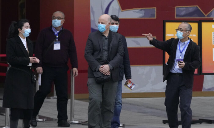 Members of the World Health Organization team including Ken Maeda (R), Peter Daszak (third from left), and Vladmir Dedkov (fourth from left) leave after attending an exhibition about the fight against the coronavirus in Wuhan in central China's Hubei province on Jan. 30, 2021. (Ng Han Guan/AP)